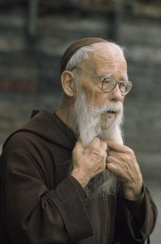 1070921.  A Franciscan friar tugs at his beard.
