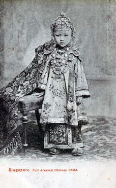 Singapore | A young Straits Chinese or nonya girl dressed for her role in  a traditional Straits Chinese wedding. She has a long, finely beaded cloak trailing to her side, a Ching-style gown, and numerous items  of jewellery including rings, and a head piece and chest ornaments based on the bride's 'sanggul kemantain' and 'dada kemantain'. | Postcard image, ca. 1910, photographer unknown.