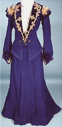 "Circa 1904 Rare and Beautiful ""Military Style"" Tailored Royal Blue Wool, Angora and Velvet 2-piece Trained Walking Suit. The jacket has a peplum attached! There are no closures on the jacket front, just the interior. waistband holds it closed. The lapels and large collar are embroidered in a floral design with ribbons and angora in lavendar-grey, off-white, light green and ""maize-color"", trimmed with deep top-stitched navy velvet."