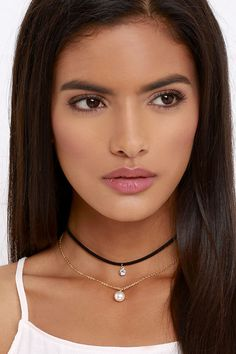 "The Pearl Power Gold and Black Choker Necklace will make any gal the leader of the pack! A slender vegan suede choker necklace (with rhinestone charm) joins forces with a dainty gold chain with faux pearl. Necklace measures 13"" around, with a 2"" extender chain."