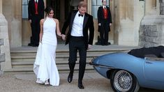 The newly married duke and duchess of Sussex, Meghan Markle and Prince Harry, prepare to leave Windsor Castle in a convertible car after their wedding in Windsor, England, to attend an evening reception at Frogmore House, hosted by the Prince of Wales, Saturday, May 19, 2018.