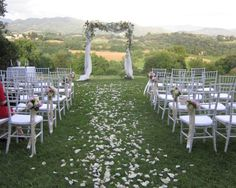 Naoko's Wedding in Tuscany, canopy, flower petals on the ground, chiavellina chairs with flower decorations