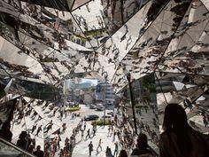 Shoppers take the escalators under multifaceted mirrors at Tokyo Plaza Omotesando Harajuku