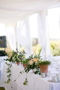Plants and lush floral arrangements in rustic pots. #creative #wedding #centerpiece #flowers