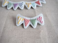 Bunting-like embroidered brooch