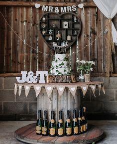 touret bois deco, idée de table gateau de marage, champetre chic, gâteau blanc sur un rondin en bois, lettres capitales mariés, fleurs dans des bouteilles en verre, bouteilles de champagne