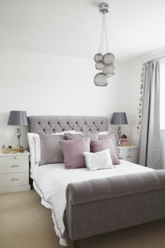 Love the combination of white bedding with grey and mauve cushions