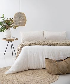 bedroom with white linens and woven basket lighting