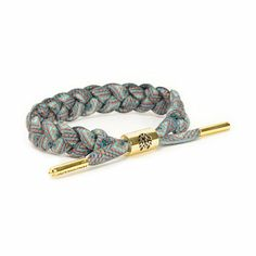 Accent any outfit with the Rastaclat Tonto Bracelet. Made with a braided shoelace in a Grey, Blue and Orange colorway for a comfortable and stylish wear, this bracelet has a Gold adjustable metal cylinder sizing piece with a debossed Rastaclat logo and Go