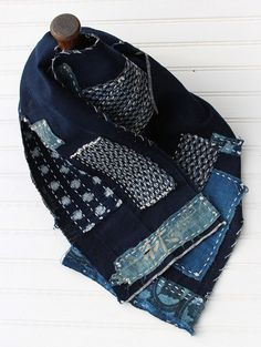 Unique and beautiful boro scarf, handmade from vintage Japanese indigo-dyed cotton fabrics. The base of the scarf is an old aizome solid indigo cotton - most recently recovered from a Japanese futon cover. This navy fabric has soft texture , white selvage along one side, and vintage white whip stitches along the other side to prevent fraying.    Each end of the scarf has several boro style patches, sashiko stitched to the base fabric. These patches include fine vintage katazome (stenciled)…