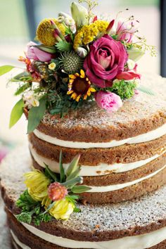 Beautiful wedding cake - carrot with exposed cream cheese frosting and wild flowers!