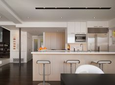 The kitchen cabinets are rift-cut white oak that was bleached to provide high contrast with the white Corian counters and dark wood floors. The island holds the sink (recessed fixtures provide task lighting), while the Miele range has a pop-up Dacor hood to keep the overall look clean. A Sub-Zero refrigerator completes the kitchen triangle