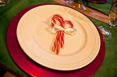White Plates, Red Chargers and Green Platemats for Christmas. Candy canes on each plate.