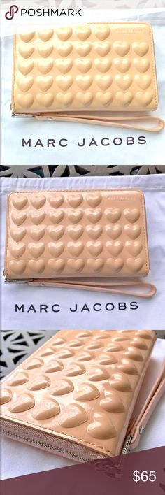 """Mark Jacobs """"Hearts"""" Phone case Wristlet / Wallet Marc Jacobs Heart Embossed IPhone Phone Wristlet Seashell Peach New $175.00  MJ Dust bag for seasonal storage -100% Authentic  Poly Coated Leather in a Satin Shell for a scratch and Moisture resistant Finish Fits the IPhone 5 / 6 / 7 non Plus sized models and similar sized phones Wrist strap Zip-around closure Silvertone hardware One inside smartphone pocket One inside zip Coin pocket Six inside credit card slots Fits iPhone 5 / 6 / 7 or…"""