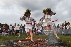 TOPSHOT - Girls wearing traditional Ukrainian clothes jump over a bonfire during the Ivana Kupala night, an ancient heathen holiday, in the Pyrogove village near Kiev on July 6, 2016. During the celebrations, dating back to pagan times, people wear wreaths, jump over fires and bathe naked in rivers and lakes. / AFP / SERGEI