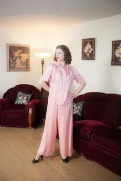 Vintage 1940s pajamas are sweet but impossibly comfortable and decadent, in a brush rayon/silk satin blend that Barbizon has named Satin Seraphim. The warm pink color says stay in today, read a book! The blouse style top, cut to be roomy and comfortably, offers subtle detailing, including six rows of top stitching along the wide collar, a flap chest pocket and gathers at each shoulder. It closes with three shell buttons. The wide pink palazzo pants closes with hidden side buttons up to the…