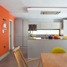 The warm and vibrant orange feature wall (try CIL DL11 Kaleidoscope 70YR 26/605) adds zest to this kitchen, livening up the grey cabinetry and bringing a sense of fun to the scheme. Limiting the colour to one wall, bar stools and the odd accessory means the look of the kitchen can easily be updated without great upheaval or expense by simple picking an alternative shade to the orange.