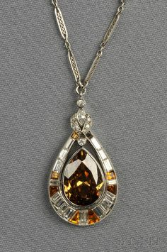 Platinum, Fancy Colored Diamond, and Diamond Pendant, set with a pear-cut fancy colored orangey brown diamond weighing 4.52 cts., framed by fancy-cut colored diamonds and baguette-, marquise-, and old E