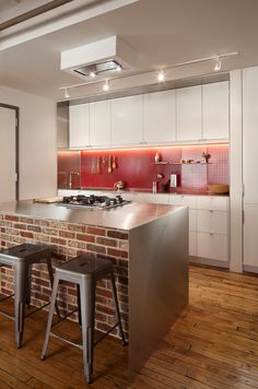 The island features a stainless steel countertop with a gas cooktop, oven, and a brick half wall.