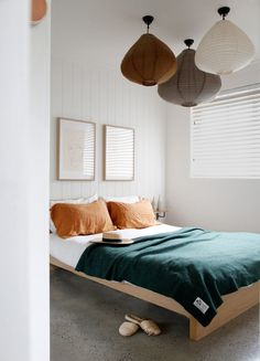 guest bedroom idea - beautiful pendant lights grouped in three, orange pillows, emerald green throw.