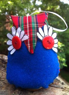 This owl has a silk hoop and can be hung as a holiday ornament on a Christmas tree or rear-view mirror or stand freely with its wood base on a fireplace or bookshelf.