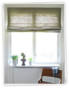 Ada and Ina -  Linen Fabrics Collection - Yellow roman blinds, pulled halfway up above a window sill with plants and sculptural decorations