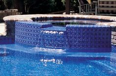 Modern Pool Design by Classic Pool & Patio featuring waterfall off gunite spa with modern pool tile.