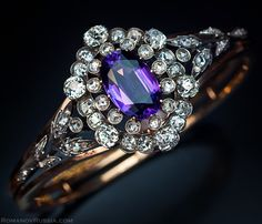 A Siberian Amethyst and Diamond Cluster Bangle Bracelet made between 1908 and 1917. A very fine antique Russian silver and polished rose gold bangle bracelet.  The front is mounted with a detachable panel set with a central 12 ct oval Siberian amethyst surrounded by a double row of old cut diamonds with an approximate total weight of 5.47 ct, flanked by two silver garlands set with rose diamonds.