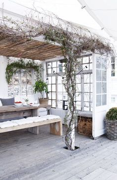 Great outdoor deck space with a vine-covered pergola and minimalist dining table with simple benches.