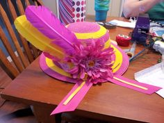 My daughter's hat for the Belmont Stakes race.  Two large quill feathers, a big pink flower with a yellow gem in the center, and two pink and yellow ribbon tails.