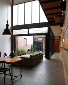 I love the raised ceilings and the large windows. I also love the down lights and what looks to be like a balcony on the right hand side. Also the fusion of indoor outdoor is really nice and although it has an urban, modern, industrial feel it still has warmth to it.