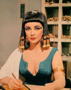 """The Egyptian Queen Cleopatra by Elizabeth Taylor. For her epic role in the 1963 film """"Cleopatra,"""" she went whole-hog in the makeup department.  She had blush, she had bronzer, she had gloss, but most of all, she had EYELINER. That majorly winged-out black liner and liberal application of shimmering blue eye shadow is now legendary and instantly recognizable. A felt-tip liquid liner pen will work best here, it gives you the most control and won't smudge."""