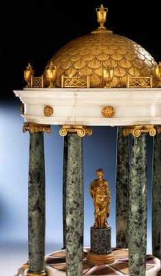 19th century Tempietto Centerpiece with parts made of marble others ormolu bronze. The domed shaped romanesque top with superb ormolu fine detailing of gratings interupted by urns and having another urn as finial, above a frieze, with applied profiles ; supported by 8 ionic columns ; having a circular base inlaid with Sienna marble & having a gilded goddess on a pedestal in it's middle - Detail.