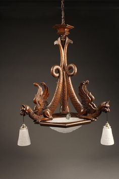 French antique chandelier with hand carved winged chymere figures with frosted Lalique style shades, circa 1920. #antique #chandelier #wood