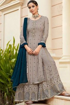 Cast a spell with this grey georgette sharara suit which makes it astonishingly charming. This round neck and full sleeve suit elaborated using zari and mirror work. Paired with georgette sharara pant in grey color with blue georgette dupatta. Sharara pant has zari and mirror work. #shararasuits #malaysia #Indianwear #weddingwear #andaazfashion Sharara Suit, Salwar Suits, Indian Salwar Kameez, Churidar, Kurti, Pakistani Suits, Pakistani Dresses, Punjabi Suits, Pakistani Street Style