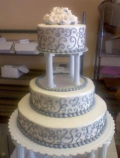 3 tier round wedding cake with 4 Roman columns supporting third tier plus white roses on top.JPG