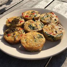 Bord met zes hartige eiermuffins gevuld met ei, spinazie, gehakt, tomaat en nog veel meer!