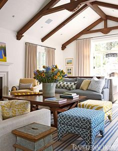 Subtle blue and yellow accents mix well in this  living space with a beam exposed ceiling.