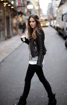 Leather jacket over striped top and black jeans, black boots.