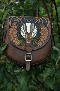 SkyRavenWolf hand carved custom leather, Wales UK www.skyravenwolf.com. (Pictured is the Lundy Bag - detailed small bag with hare and white pine design scattered with bees)
