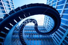 Spiral stairs in front of modern architecture Royalty Free Stock Photo. Get wonderful discounts on images, illustrations, Videos and music clips at iStockphoto with Coupon.