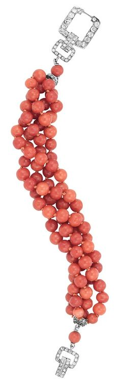 An Art Deco Four Strand Coral Bead and Diamond Torsade Bracelet, Circa 1920. Platinum, composed of deep orange and oxblood coral beads approximately 6.1 to 5.7 mm., completed by two diamond-set rondels and a buckle link clasp set with old-mine cut and single-cut diamonds. #ArtDeco #bracelet