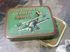 Vintage 1920s tin of Squadron Leader, one of the best sold blends by Sam Gawith. While the tin design has not changed substantially throughout the years, the emblematic Royal Airforce biplane design still being printed on current tin labels, the blend has evolved to a new recipe that, unlike the original, lacks the addition of Perique. [ Photo credits: A11en, via Flickr ]