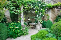 beautiful walled garden; love the romantic setting created under the plant covered pergola