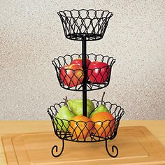 """DECORATIVE WIRE BASKET  Product # HC2137  $19.98 CAD - Holds and displays your favourite edibles and more! Decorative table-top stand features a trio of black wire baskets mounted on a sturdy iron rod and supported with 4 scrolled feet. Perfect for ripening fresh fruits and vegetables or showing off seasonal decorations and dried flowers. 17-1/2""""H x 9-1/2""""Diam."""