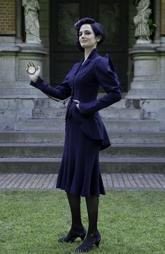 Eva Green as Miss Peregrine in Miss Peregrine's Home for Peculiar Children. This images gives a very good view of her character's attire from the blue (!) jacket, skirt and stockings to her striped (?feathers) shoes. You also get to see the pocket watch resetting time piece. From the Herald Sun