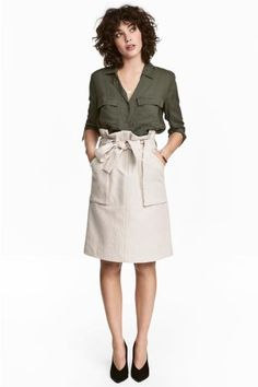 Cargo skirt in a woven cotton blend with patch front pockets, a wide tie belt at the waist, zip fly and hook-and-eye fastening.