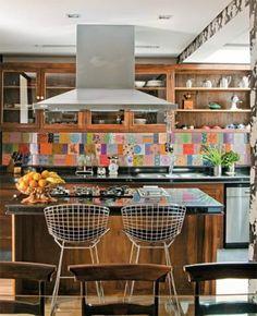 Feitos de canela de demolição (Paineira Móveis), os armários mesclam portas de madeira e de vidro e nichos abertos, o que torna o visual dos módulos mais leve. Coifa sob medida executada pela Pulsar, banquetas Bertoia da Tok & Stok.