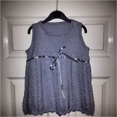 Grey/blue knitted lace dress with silver ribbon.