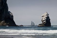 Old style sail ship sails inside a buoy, between Morro Rock (Left) and Pillar Rock (Right) off Morro Strand State Beach just north of Morro Rock, Morro Bay, CA